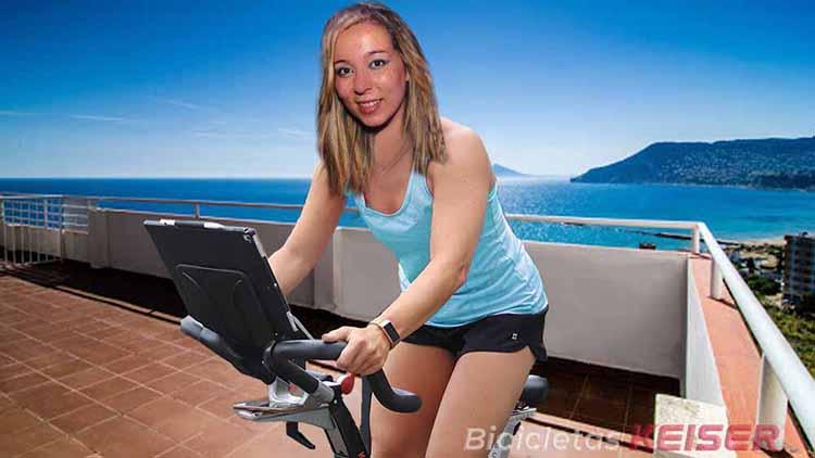 mujer entrena en casa con bicicleta keiser